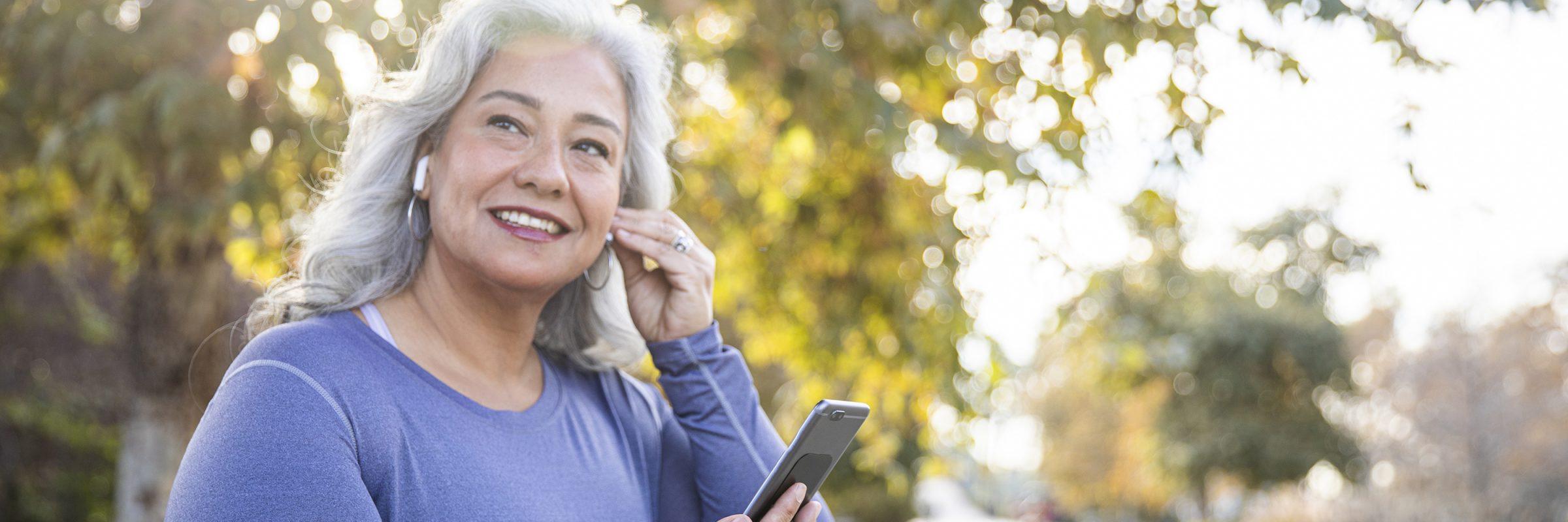 Frau mit Kopfhörer macht Sport über App