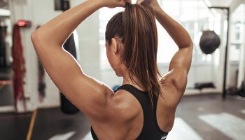 Frau mit Zopf und Rückenmuskeln